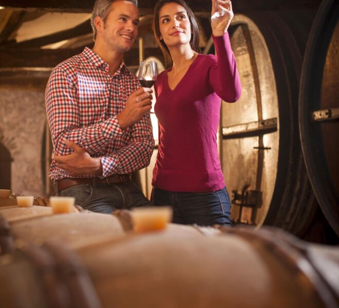Couple tasting a glass of white wine in a traditional cellar sur